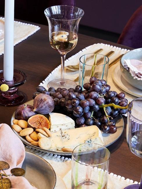 Tagliere con formaggio uva e fichi con un bicchiere abbinato