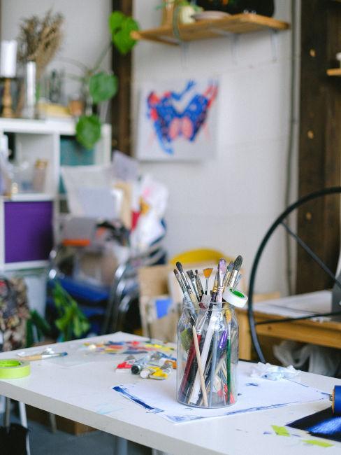 vaso con pennelli su tavolo bianco studio artistico