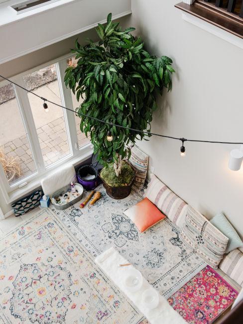 stanza vista dall'alto con tappeti, cuscini e piante
