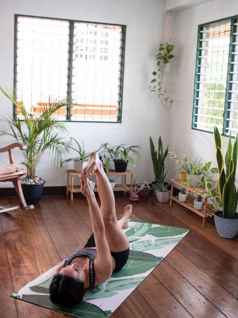 ragazza sdraita su un tappetino che pratica yoga