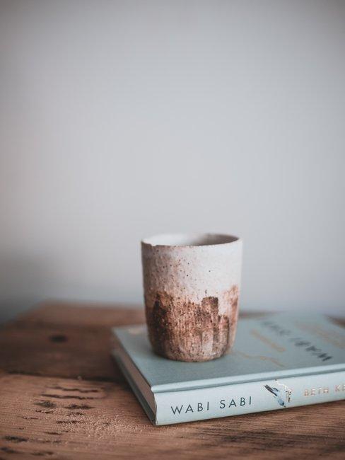 tavolo in legno con libro wabi sabi e tazza di ceramica fatta a mano