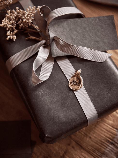 Confezione regalo scura con nastro e decorazione