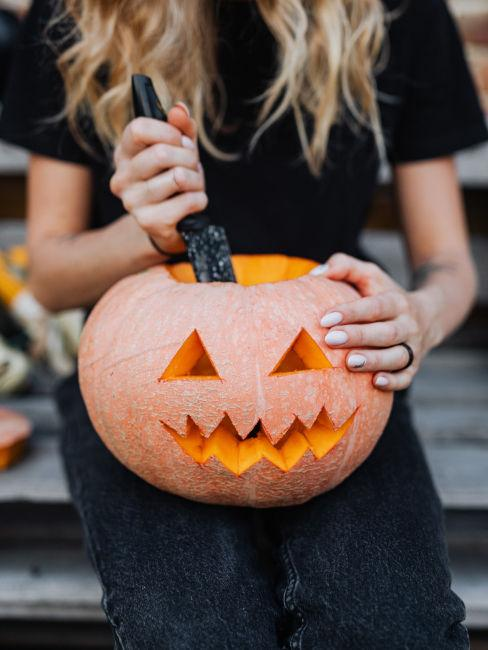 mani ragazza che intaglia zucca per halloween