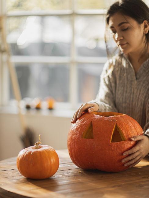 ragazza che realizza una zucca per halloween