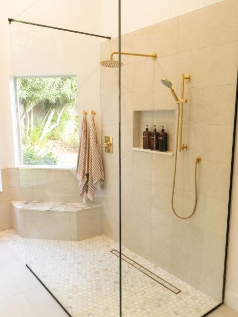 doccia chiara con elementi oro e finestra