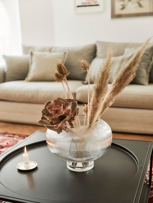 Vaso in vetro con fiori secchi, sullo sfondo divano beige