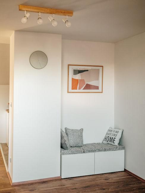 parete bianca con panca e cuscini