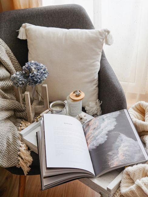 libro aperto appoggiatosu poltrona con cuscino e coperta
