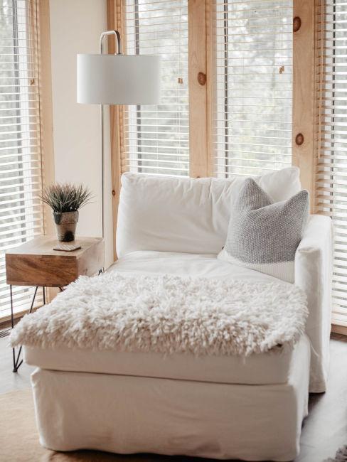poltrona bianca con tavolino in legno e lampada