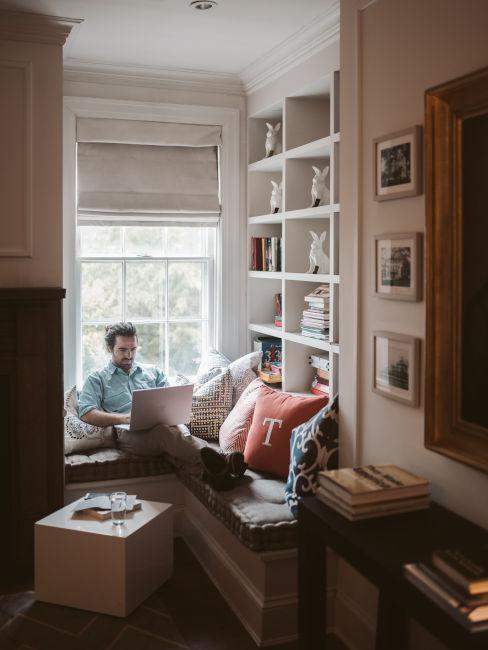 ragazzo che lavora al computer sotto alla finestra