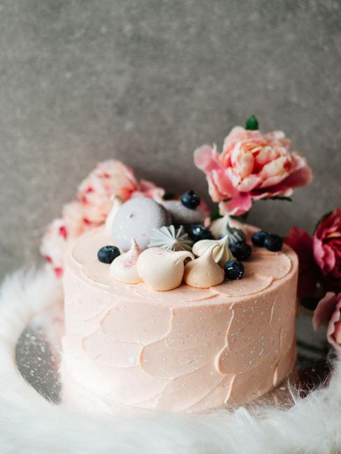 torta decorata con meringhe, bacche e fiori