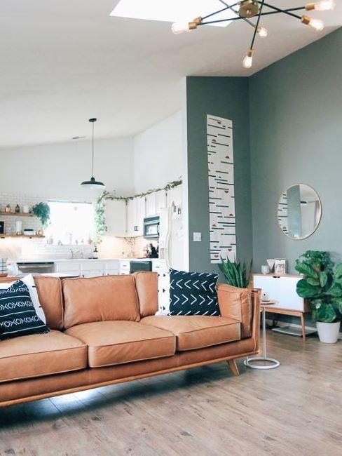 soggiorno con divano in pelle marrone e parete in cartongesso verde