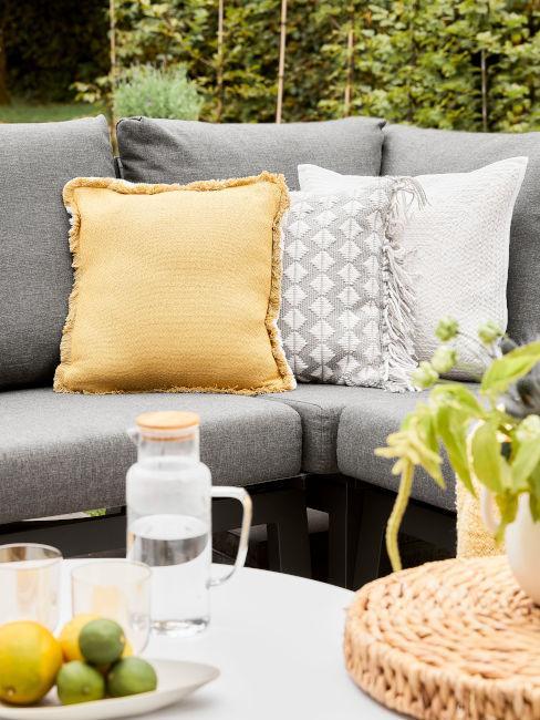 divano da esterno grigio con cuscino giallo