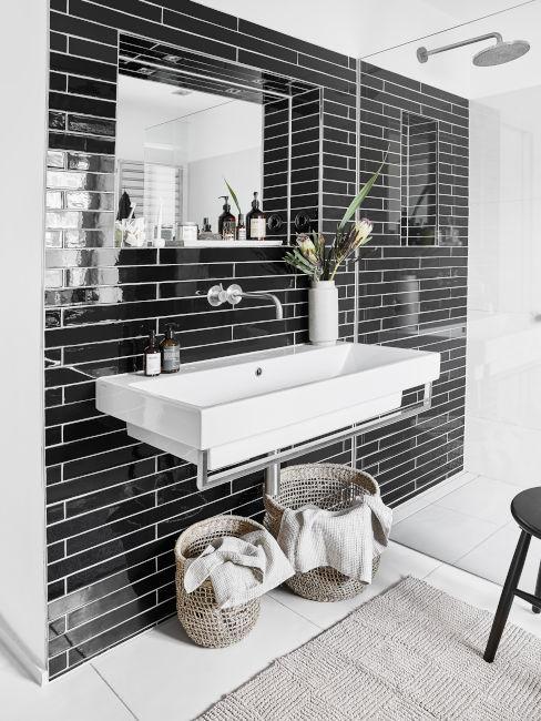 parete con piastrelle nere e lavandino bianco