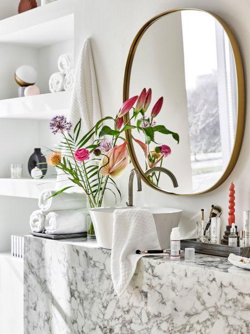 bagno in marmo con vaso di fiori e specchio dorato