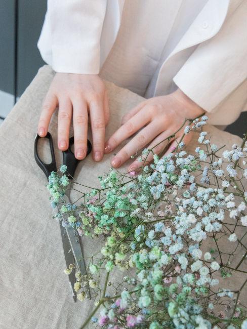 mani di ragazza che realizzano decorazioni con fiori