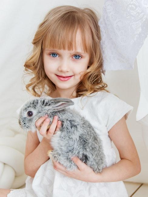 bambina bionda con coniglio nano