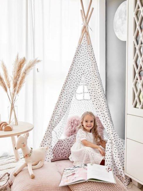 bambina che gioca con tenda in cameretta