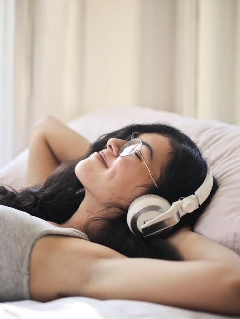 ragazza distesa aletto che ascolta audiolibri