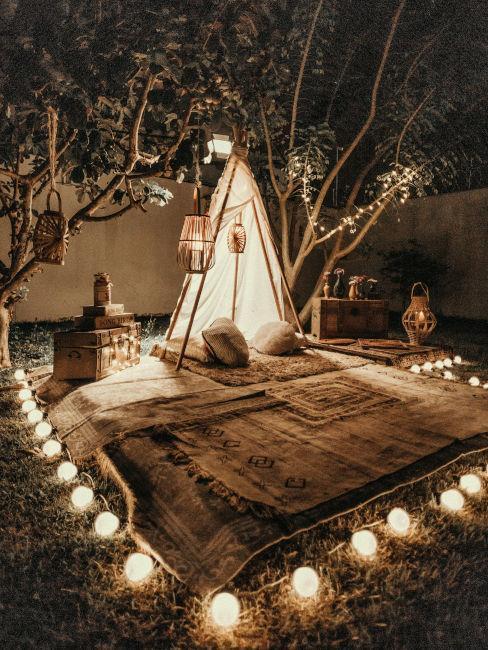 tenda circondata da tappeti e lucine