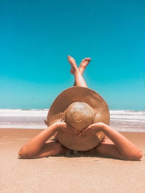 donna in spiaggia che prende il sole con cappello di paglia