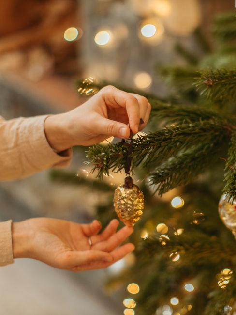 mani che appendono pallina all'albero di natale