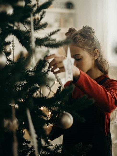 Bambina decora l'albero di Natale
