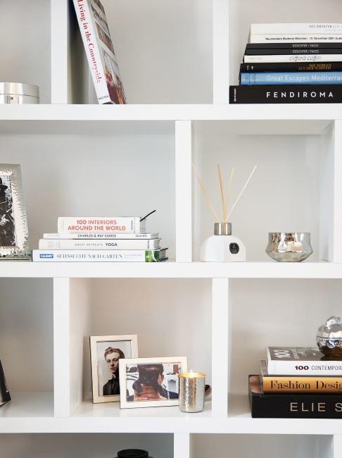 libreria con scaffalature bianche e oggetti decorativi come idea per arredare il sottoscala