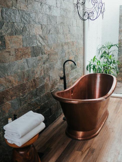 Bagno con parquet e rivestimento effetto pietra