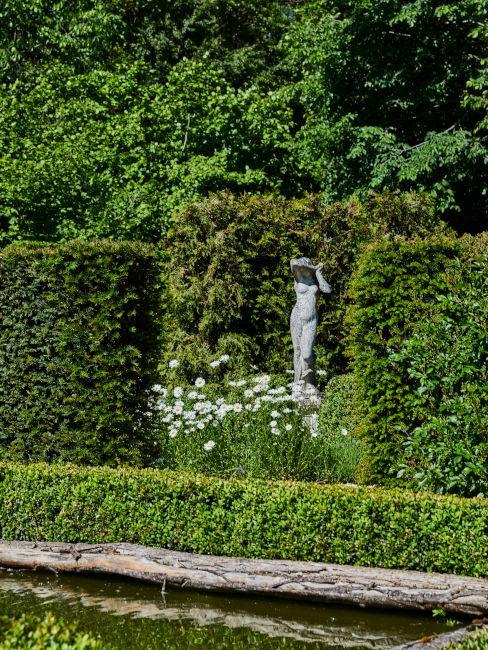 Statua da giardino circondata da siepi