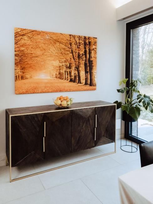 Credenza in legno scuro con quadro autunnale