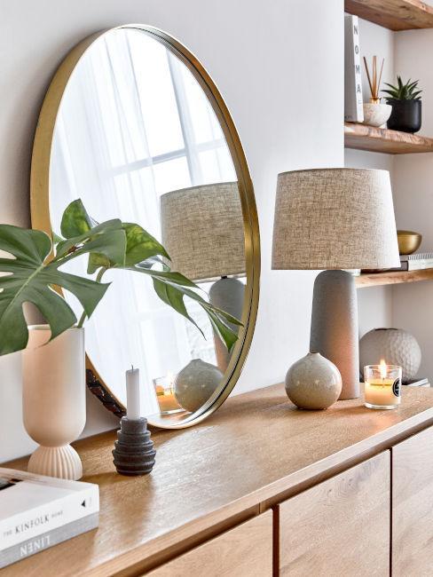 Specchio tondo su credenza in legno chiaro