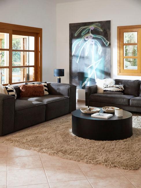 divani antracite con tavolino scuro centrale e tappeto chiaro