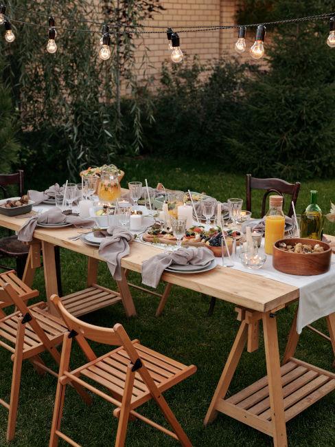 cena estiva in giardino con tavolo e sedie di legno