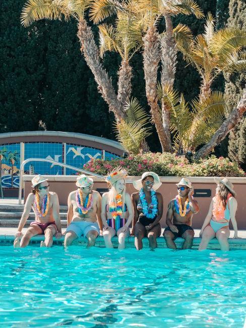 gruppo ragazzi con collane di fiori in piscina