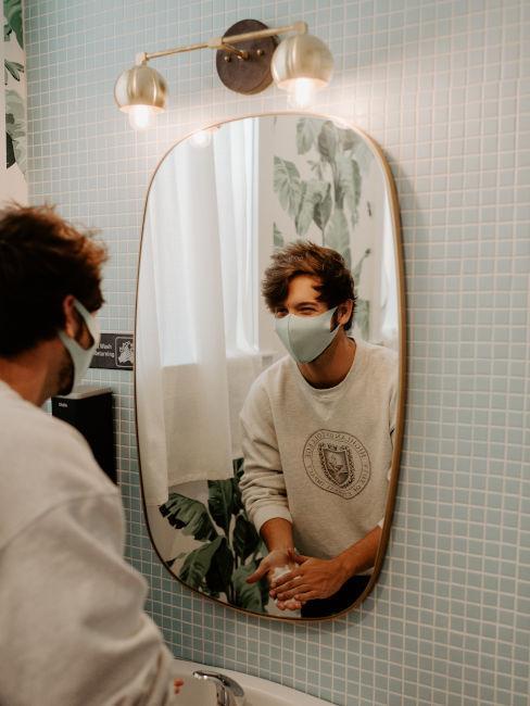 ragazzo con mascherina che si guarda allo specchio