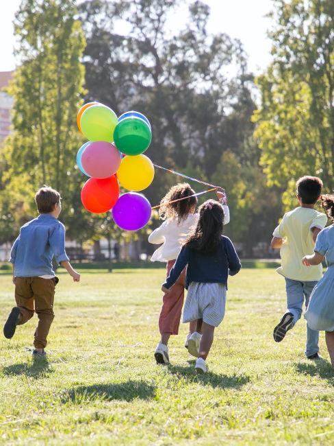 bambini che giocano all'aperto con palloncini