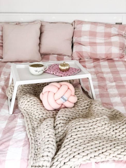 coperta in lana beige su letto con lenzuola rosa