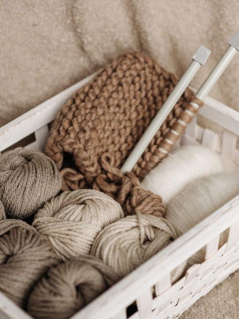 cassetta di legno con gomitoli di lana e ferri
