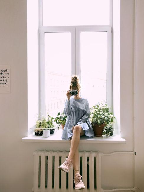ragazza seduta su finestra con vestito azzurro