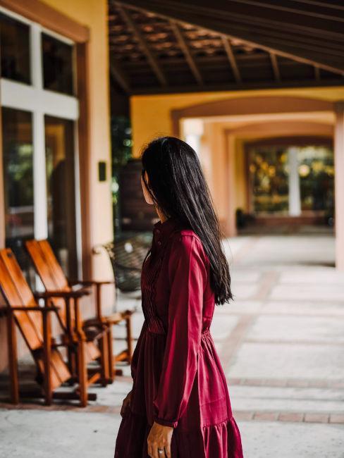 ragazza castana con vestito lungo color rosso scuro