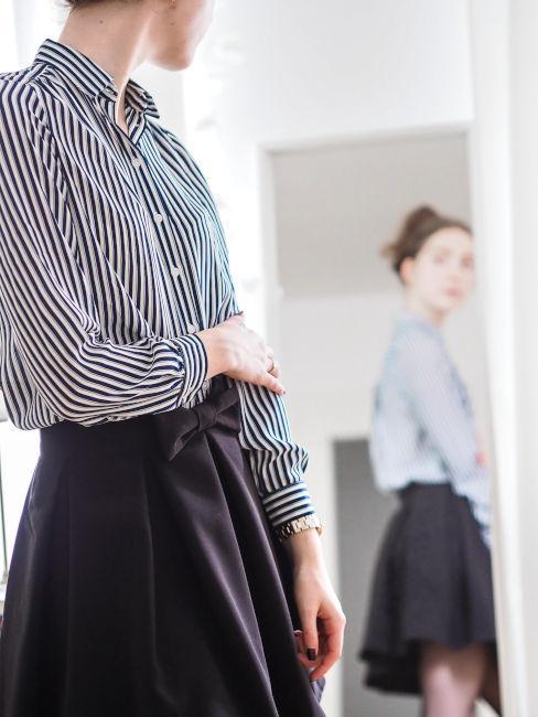 ragazza allo specchio con camigia a righe e gonna nera