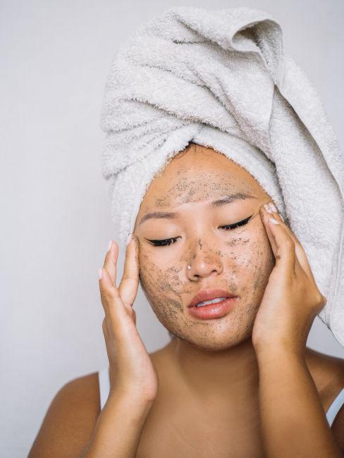 ragazza che si applica uno scrub viso