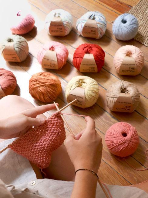 ragazza che lavora a maglia e gomitoli di cotone