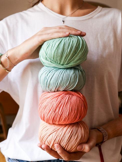 mani di ragazza che tengono gomitoli di cotone colorati