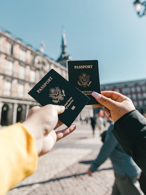 mani di persone che mostrano i passaporti