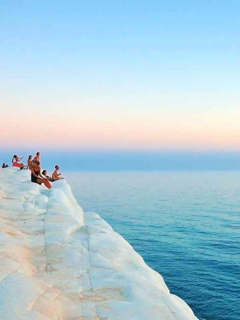 persone che guardano l'alba alla baia dei turchi in sicilia