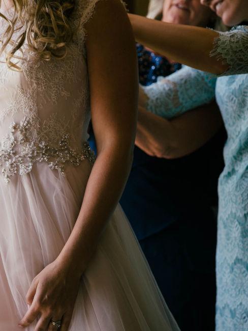 mamma che aiuta figlia a chiudere il vestito da sposa