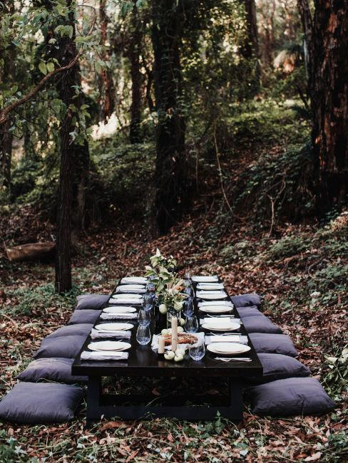 tavolo di legno nel bosco apparecchiata con cuscini