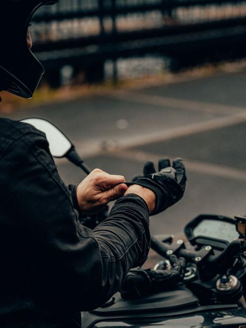 ragazzo che si infila i guanti da moto